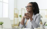 Office Work. Smiling Black Business Lady Sitting At Laptop At Workplace Indoor. Copy Space